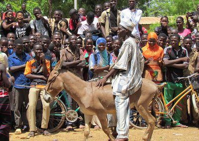 This young man displayed his traditional clothes while riding on a donkey.