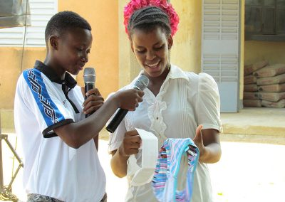 Mom gives daughter a demonstration about using sanitary pads.
